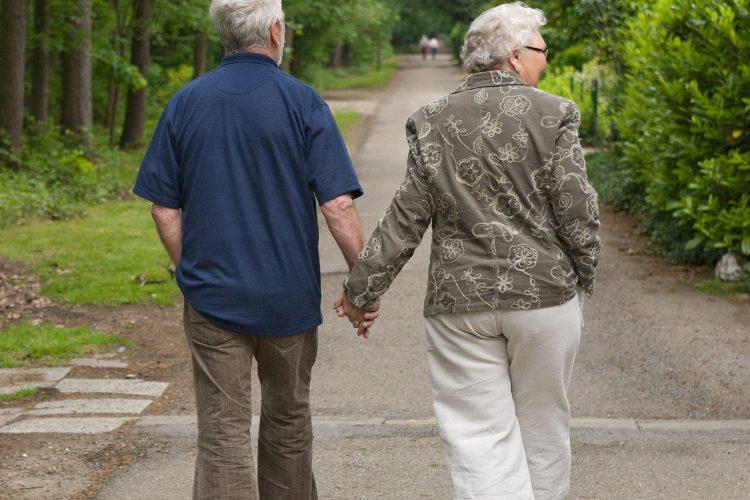 outside portrait of an elderly couple walking along a forest road